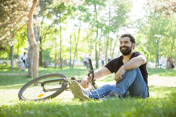 Bearded man next to his bicycle resting on the ground - Stock Photo - Images
