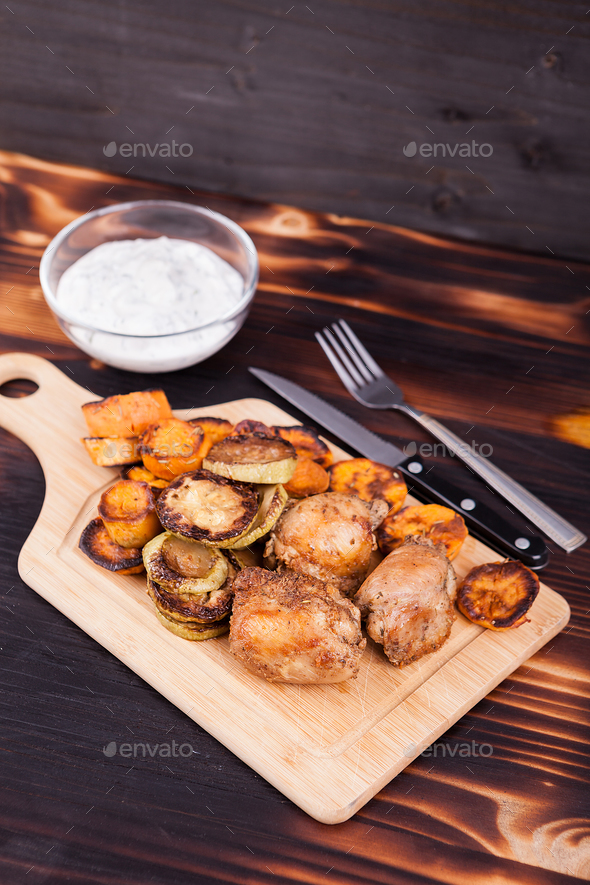 Grilled chicken next to fried zucchini and sweet potatoes - Stock Photo - Images