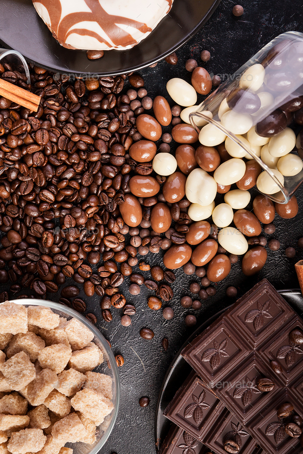 Spilled glasses with coffee beans and peanuts in chocolate - Stock Photo - Images