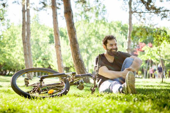 Young bearded man smiles to the camera sitting on the ground in the grass - Stock Photo - Images