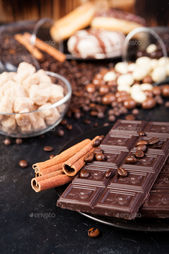 Chocolate tablets next to cinnamon rolls and other sweets and candies - Stock Photo - Images
