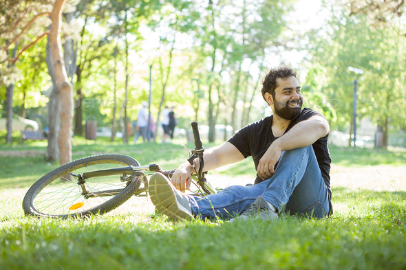 Man next to his bicycle resting on the grass - Stock Photo - Images