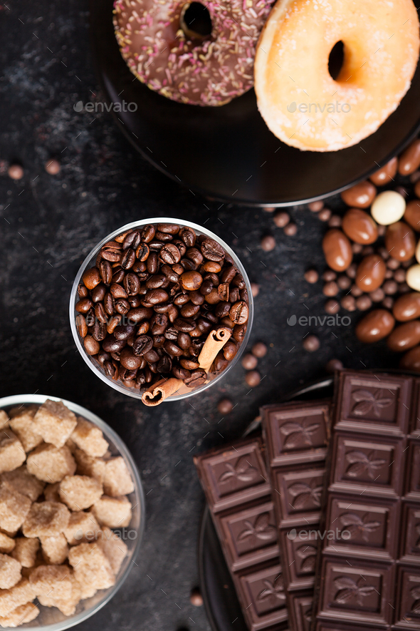 Coffee beans in a glass with cinnamon sticks next to different types of candies - Stock Photo - Images