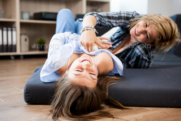 Cute teenage girl and her middle aged mother playing with each other - Stock Photo - Images