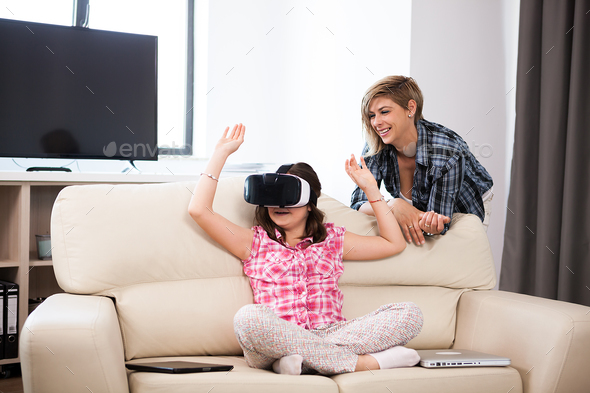Happy kid wearing a virtual reality headset and plays games - Stock Photo - Images