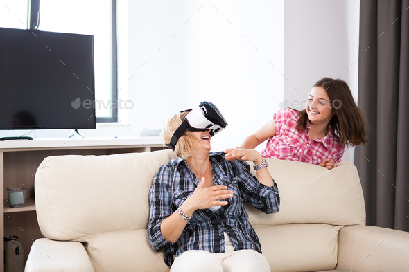 Happy middle aged woman with a VR headset on playing games - Stock Photo - Images