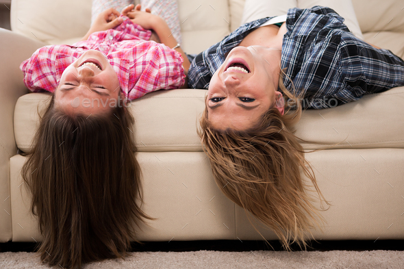 Beautiful mother with her cute daughter lying on the couch with their head upside down - Stock Photo - Images