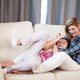 Happy teenage child daughter and her mother laughing on the couch - PhotoDune Item for Sale