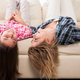 Beautiful mother with her cute daughter lying on the couch with their head upside down - PhotoDune Item for Sale