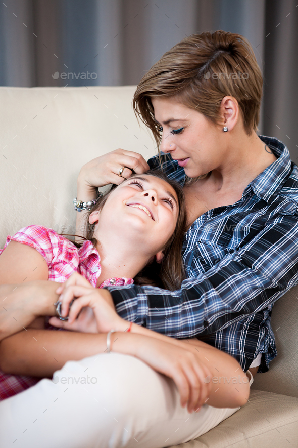 Mother and her beautiful child daughter talking to each other, sitting in the living room - Stock Photo - Images