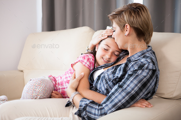 Mother kisses her daughter on the forehead - Stock Photo - Images