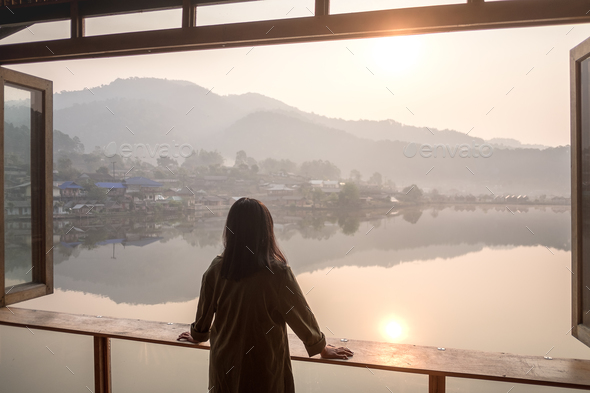Girl looking out at lake in the morning - Stock Photo - Images