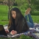 Asian Girl Working with Her Notebook Lying on Lawn - VideoHive Item for Sale