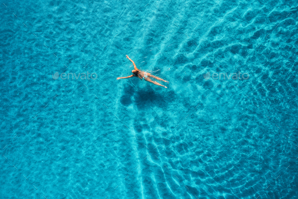 Aerial view of swimming woman in mediterranean sea at sunset - Stock Photo - Images