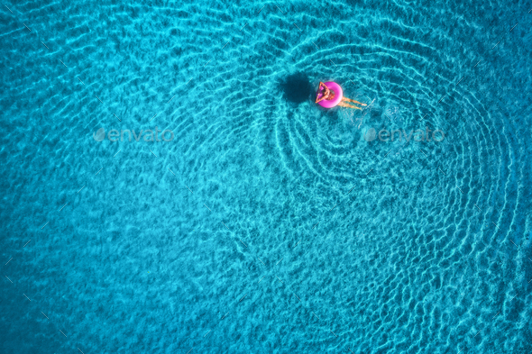 Aerial view of young woman swimming in the sea with transparent water - Stock Photo - Images