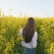 View of Young Girl Going in Colza Field - VideoHive Item for Sale