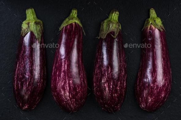Pink or purple aubergine on dark slate - Stock Photo - Images