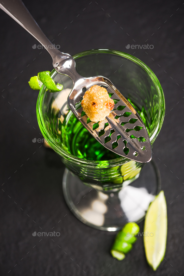 Carmelized sugar cube over green Absinthe vodka - Stock Photo - Images