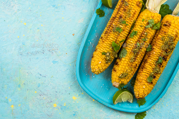 Serving grilled corn cob on vibrant pastel board - Stock Photo - Images