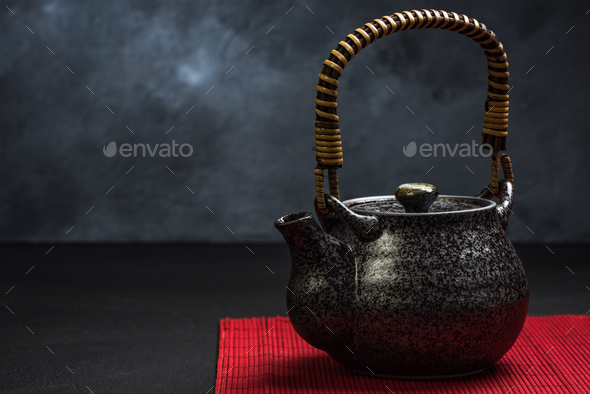 Traditional Tea pot on red bamboo - Stock Photo - Images