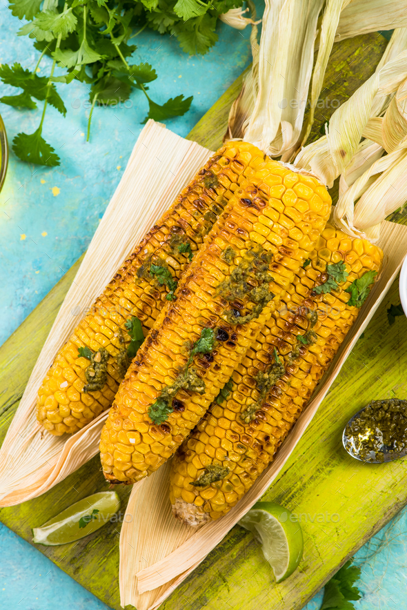 Serving grilled corn in husk with pesto and lime and herbs - Stock Photo - Images