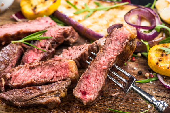 Grilled beef steak slice, close up on fork - Stock Photo - Images