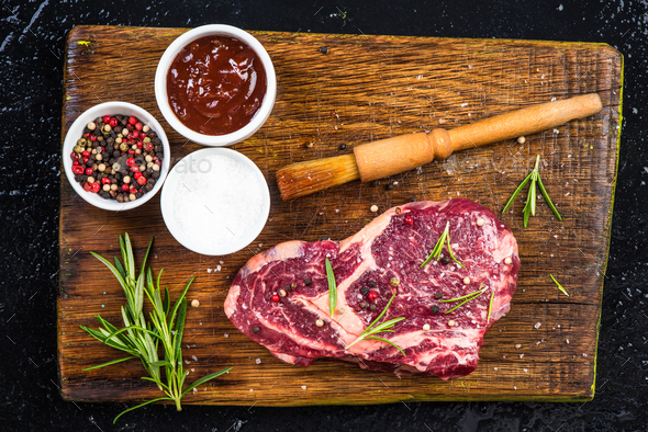 Meat piece with herbs and spices on wooden board - Stock Photo - Images