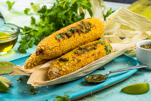 Grilled corn in husk,pesto and coriander - Stock Photo - Images