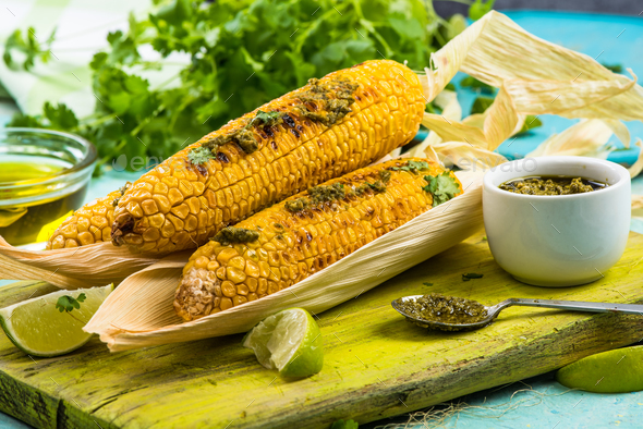 Whole corn cob grilled in husk - Stock Photo - Images