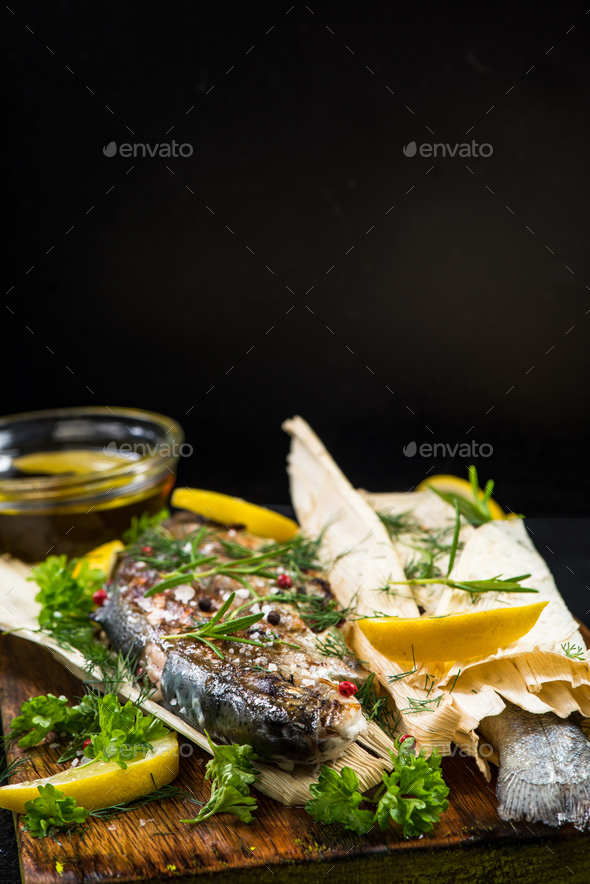 Fish grilled and served in corn husk with herbs - Stock Photo - Images