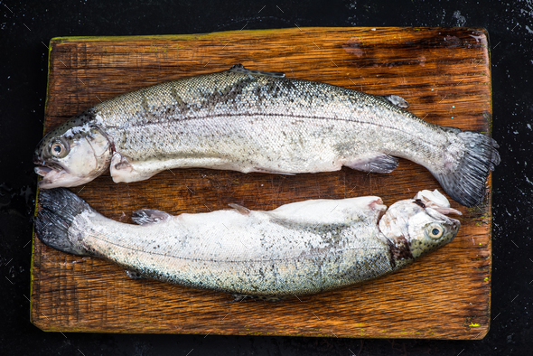 Raw trout fresh fish on wooden board,top view - Stock Photo - Images