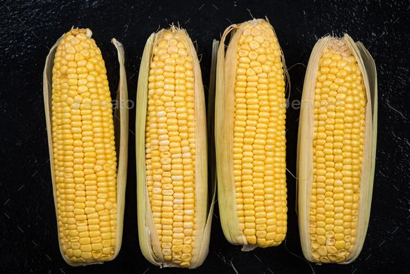 Whole sweetcorn cob on dark background - Stock Photo - Images