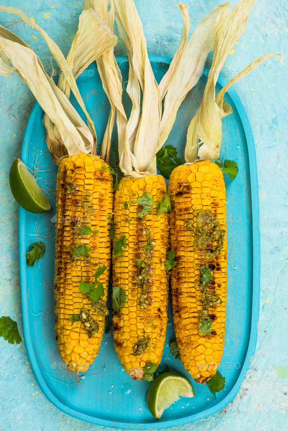 Colorful image of grilled corn with lime and herbs - Stock Photo - Images