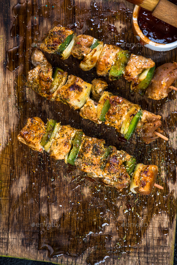 Grilled meat and vegetable skewers on wooden board - Stock Photo - Images