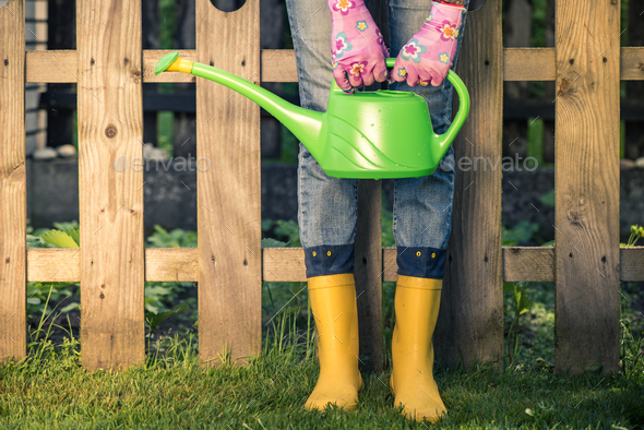 Gardener in yellow wellies and watering can - Stock Photo - Images