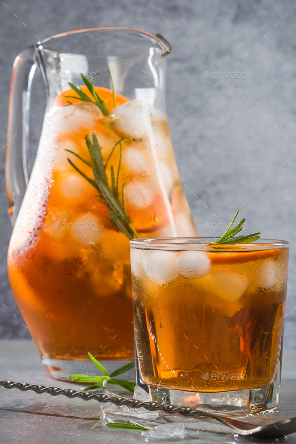 Ice cold tea in pitcher and glass with rosemary garnish - Stock Photo - Images