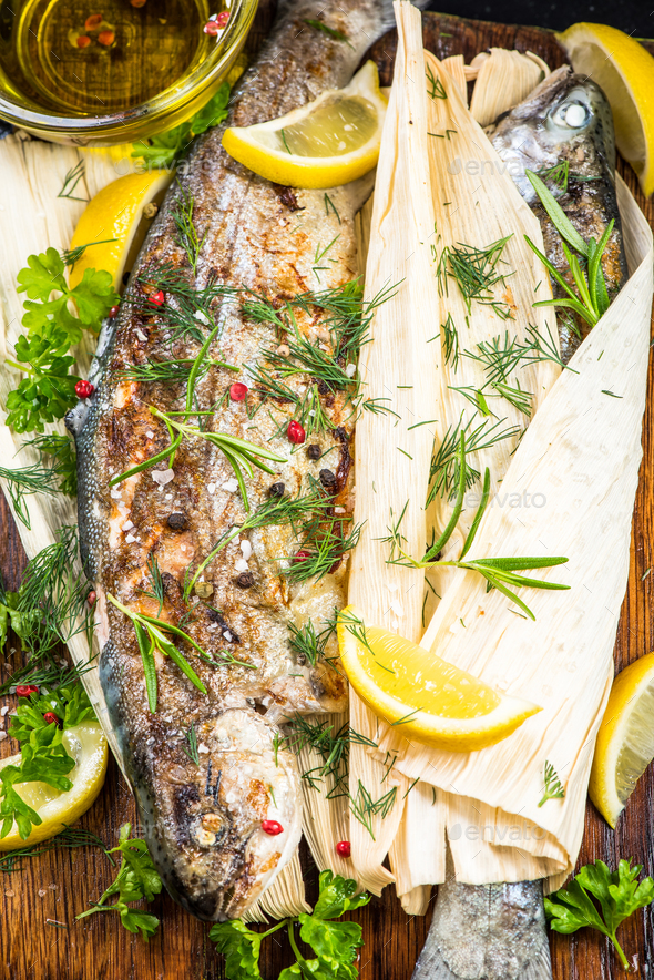 Fresh fish grilled in corn husk, healthy eating - Stock Photo - Images
