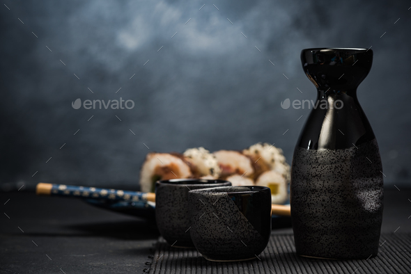 Drinking traditional sake and eating sushi - Stock Photo - Images