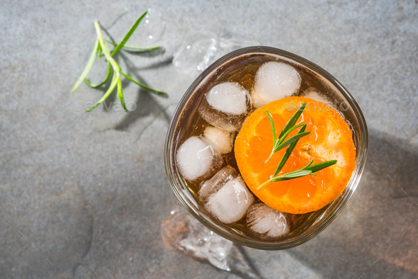 Glass with ice cold tea beverage and rosemary garnish - Stock Photo - Images