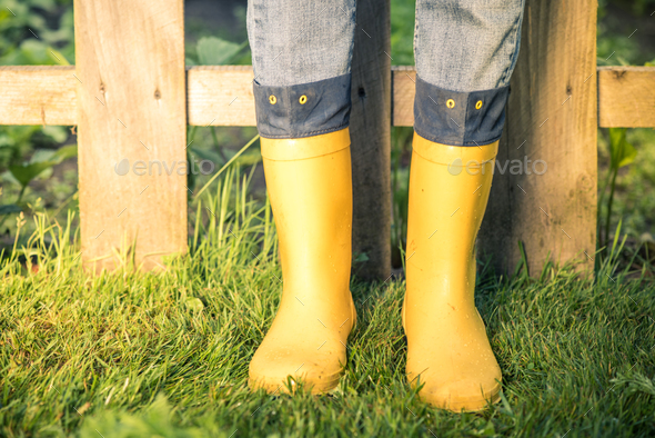 Yellow wellies and jeans in garden,toned image - Stock Photo - Images