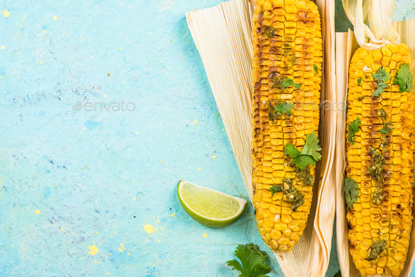 Grilled corn in husk with lime, copy space - Stock Photo - Images