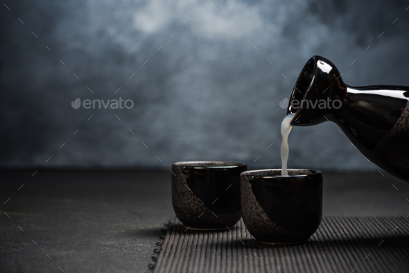 Pouring sake into sipping ceramic bowl - Stock Photo - Images
