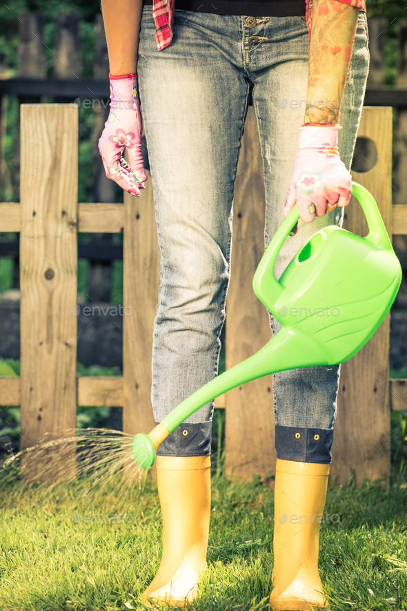 Tattooed woman watring plants in garden wearing wellies - Stock Photo - Images