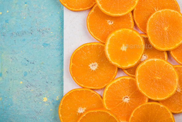 Orange slices on marble board and blue table - Stock Photo - Images