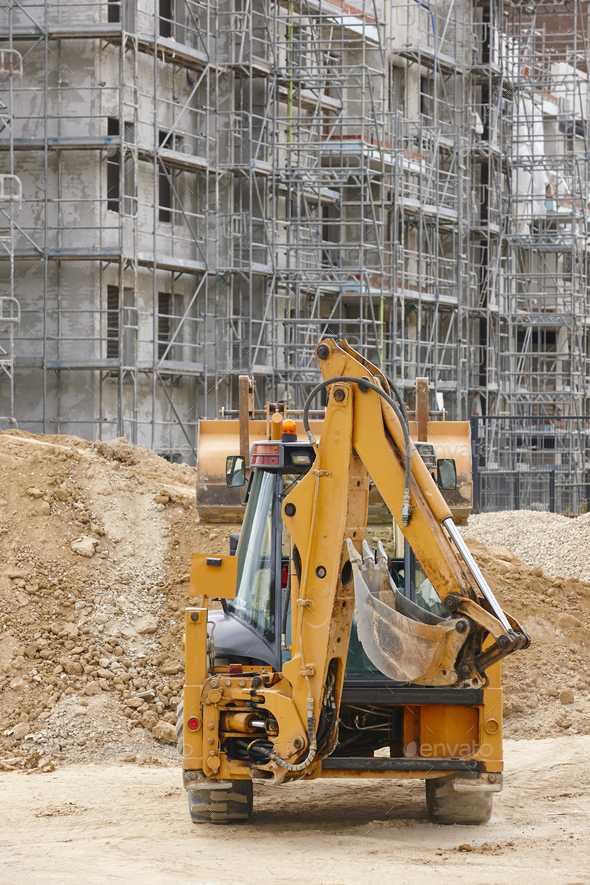 Excavator on a construction site. Building in progress. Architecture. Vertical - Stock Photo - Images