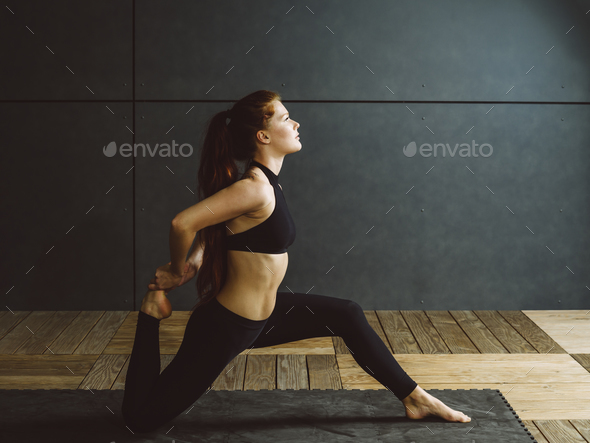 Redhead woman doing kneeling quad stretch - Stock Photo - Images