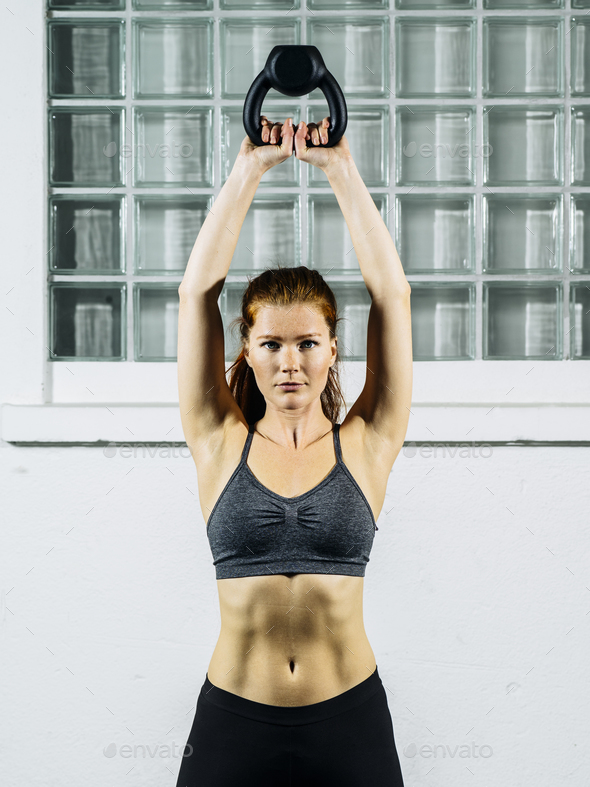 Young redhead woman exercising with a kettlebell - Stock Photo - Images