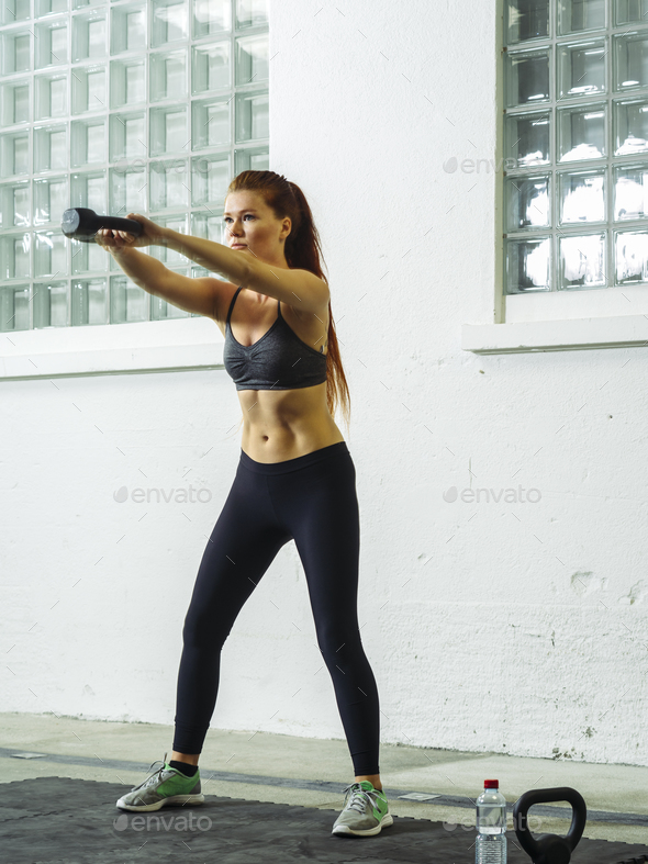 Beautiful young redhead exercising with a kettlebell - Stock Photo - Images