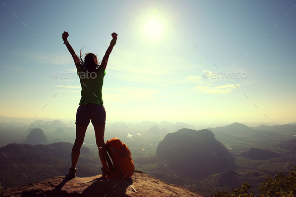 Successful hiker outstretched arms on sunrise mountain top - Stock Photo - Images