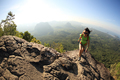 Woman backpacker climbing up on cliff edge - PhotoDune Item for Sale